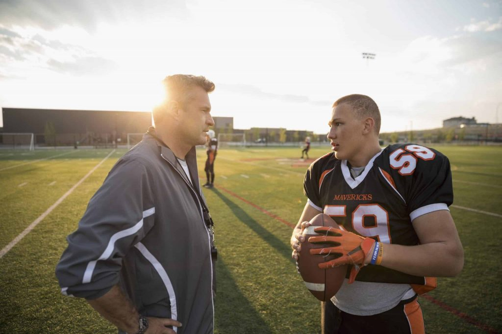 Football coach with player
