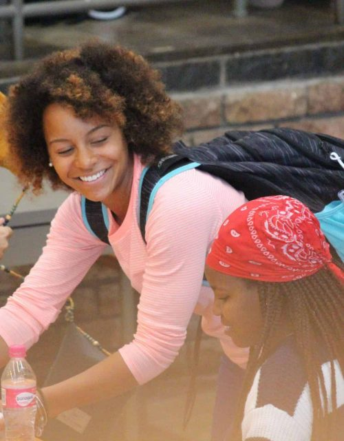 young woman wearing a backpack and smiling at a young girl