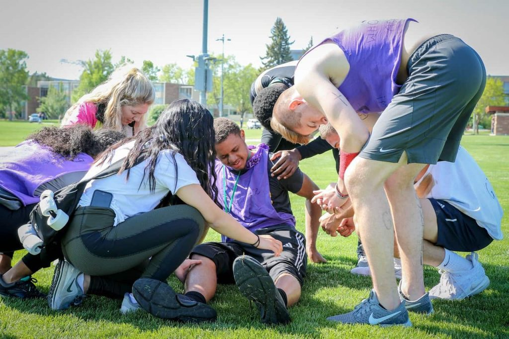 Hurt athlete surrounded by others who are praying and assisting