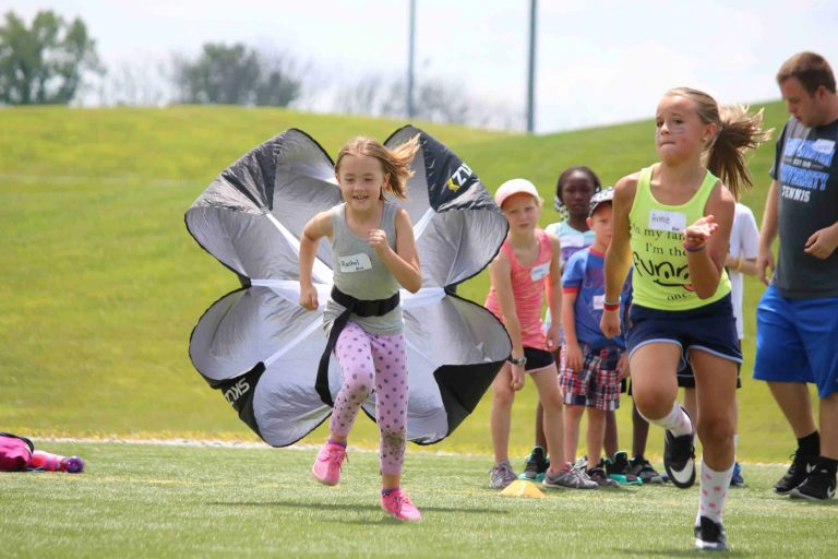Girl sprinting with parachute