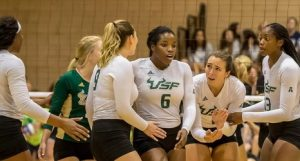 5 University of S. Florida women's team members talking to each other on a court during a game