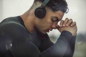 Young man wearing black headphones with eyes closed praying