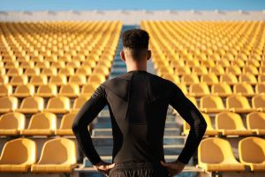 Male young adult athlete facing stadium steps