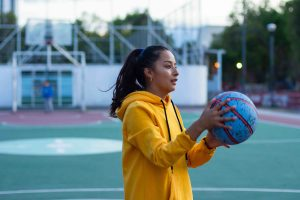 Young woman athlete in a yellow hoodie holding a blue basketball