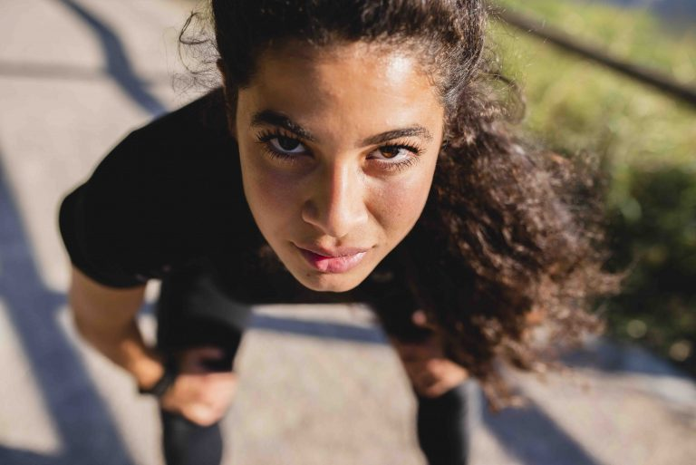 closeup of girl's intense face looking at camera from a bent-over position ready to spring forward on a road.