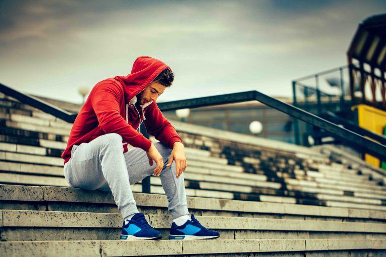 lone athlete sitting in bleachers looking down