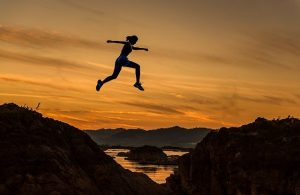 silhouette of a female jumping high in air between two mountains with orange sky and lake in background