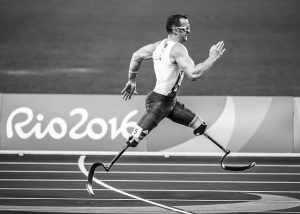 Man with two prosthetic legs running on a track with Rio2016 written on the photo.