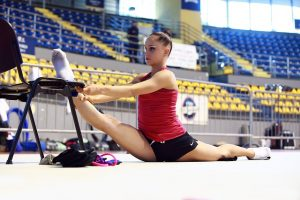 girl in red shirt stretching into splits with one foot up on a chair