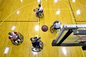 male wheelchair basketball players on a court, one is throwing the ball up toward the backboard