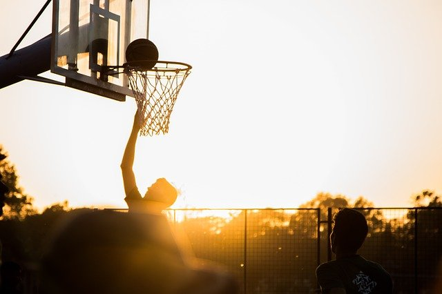 basketball player with hand up and ball above the net on an outdoor court with sun on horizon behind him