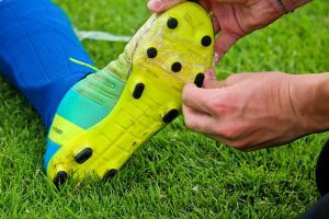 one hand on the top and one hand touching a spike on the bottom of a shoe worn by someone sitting on grass