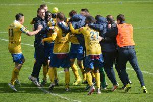 men's soccer team hugging happy on field