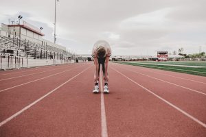 Facing an athlete bent over at the waist looking down in the middle of a track.