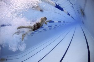 man swimming in lanes seen from behind him underwater