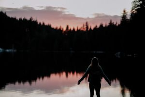 Silhouette from back of a female in shorts with arms out to the side in front of a lake and silhouette of trees and mountains.