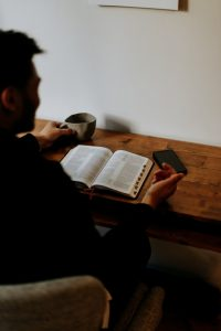 Looking over the shoulder of a shadowy man reading a Bible at a desk.