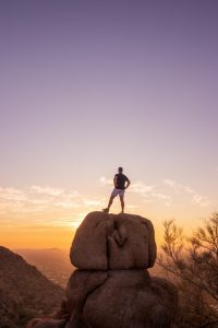 Man with his back to the camera looking toward the horizon while standing on top of a large rock.