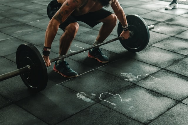 person squatting down, about to lift heavy weights