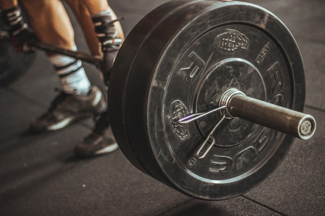 large weight on barbell barely lifted off the floor