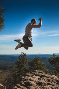 Man jumping high above rocks, trees, mountains and skyline.