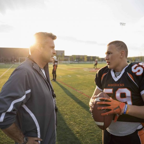 Coach and teenage boy high school football player talking on football field at sunset