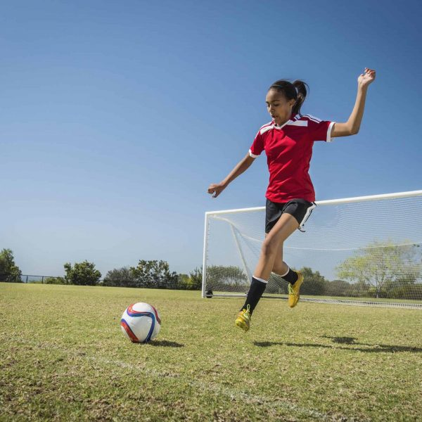 Mixed race soccer player kicking ball on field