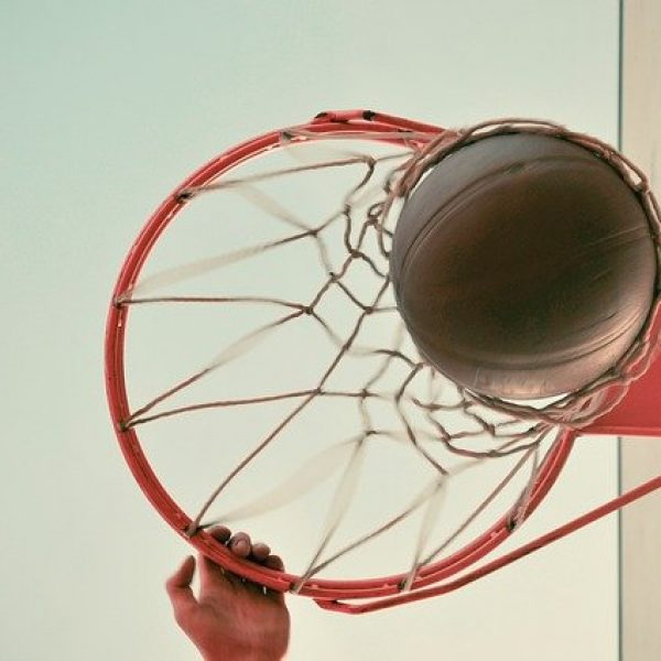 Looking up at hand on basketball rim, ball dropping through the net