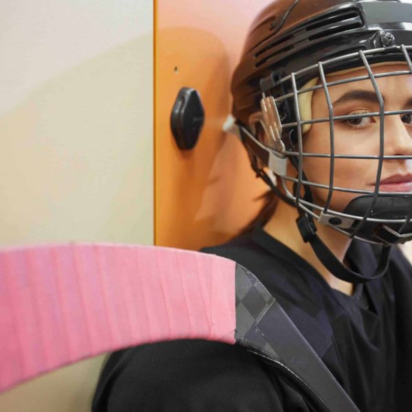Closeup portrait of beautiful young woman wearing hockey gear and looking at camera while posing in locker room, copy space
